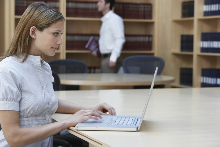 one person with others: Office worker using laptop in legal office side view