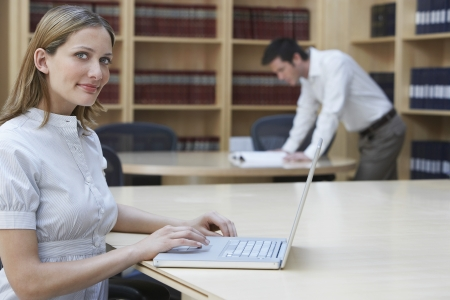 law library: Office worker using laptop in legal office portrait