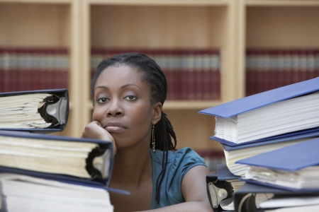 legal office: Office worker sitting behind stacks of documents in office portrait