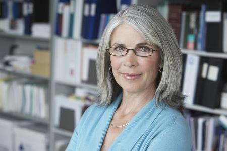 50s women: Business woman in office portrait LANG_EVOIMAGES