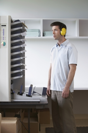 photocopier: Man wearing headphones standing by photocopier