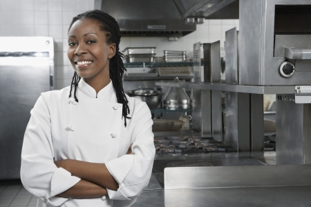 Female chef with arms crossed in kitchen portrait Stock Photo