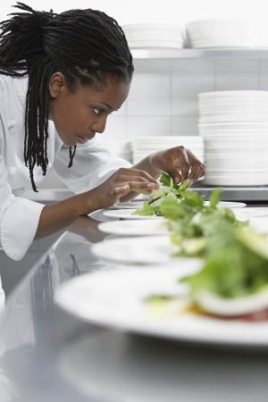 appetiser: Female chef preparing salad in kitchen