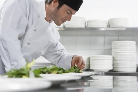 gorro chef: Cocinero de sexo masculino que prepara la ensalada en la cocina