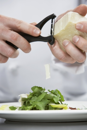 grating: Male chef grating cheese over salad mid section LANG_EVOIMAGES