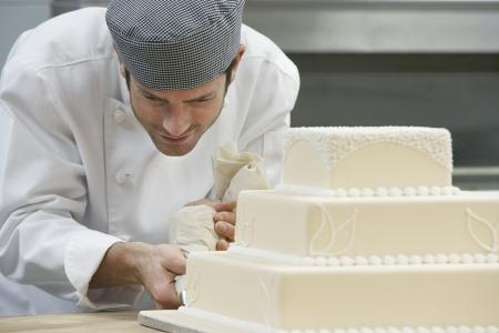 cake decorating: Male Chef guinda del pastel de bodas en la cocina