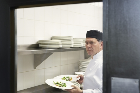 view through door: Man chef holding plates of food in kitchen