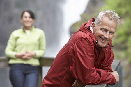 british man: Man and woman in mountains focus on man leaning on railing