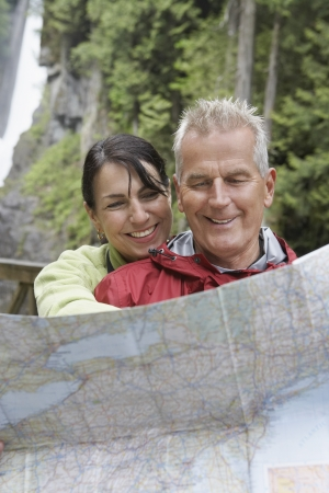 ecotourism: Man and woman reading map waterfall in background