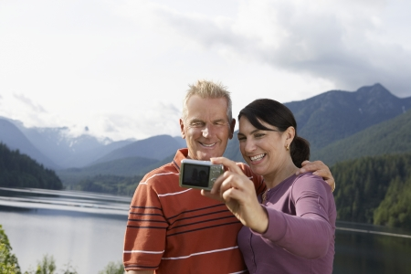 Couple photographing selves mountains in background Stock Photo - 19078125