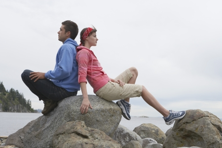 contented: Couple sitting back to back on rocks by ocean