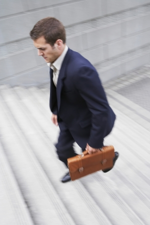 elevated view: Business man carrying briefcase ascending steps elevated view LANG_EVOIMAGES