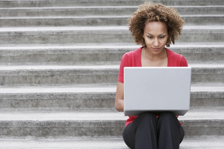 mixed race woman: Woman using laptop on steps