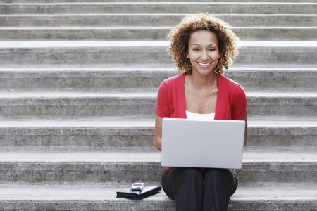 mixed race woman: Woman using laptop on steps portrait