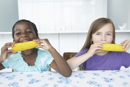 hair blacks: Two girls (5-6) sitting at table eating corn cobbs