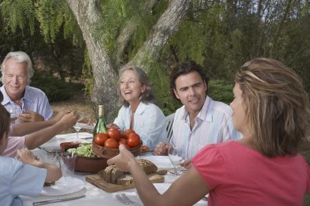familia cenando: Familia de tres generaciones de ni�os (6-11) comedor en el jard�n