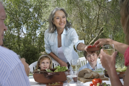 Three-generation family including two children (5-6) eating at garden table Stock Photo - 19078371