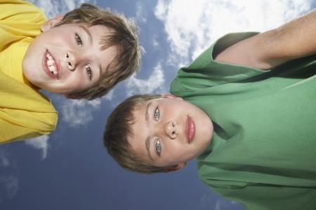 bending down: Retrato de dos ni�os (6-11) inclin�ndose vista desde abajo