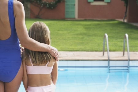 two piece swimsuits: Mother and daughter (5-6) in swimwear by pool back view