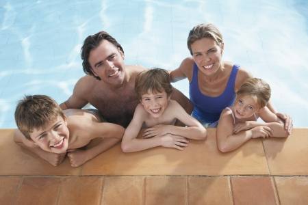 two piece swimsuits: Portrait of family with three children (5-11) in swimming pool smiling LANG_EVOIMAGES