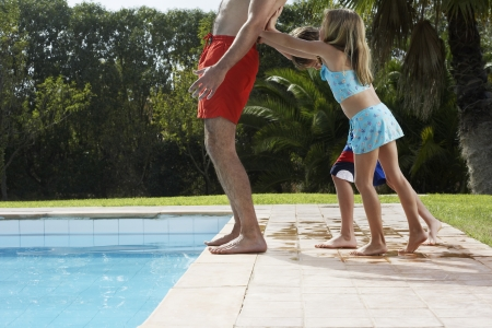 pool side: Children (5-6) pushing father into swimming pool