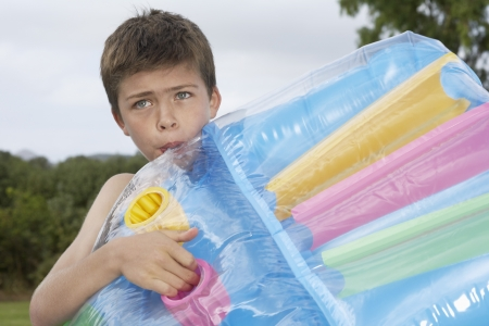 pool preteen: Boy (10-12) blowing up air mattress LANG_EVOIMAGES
