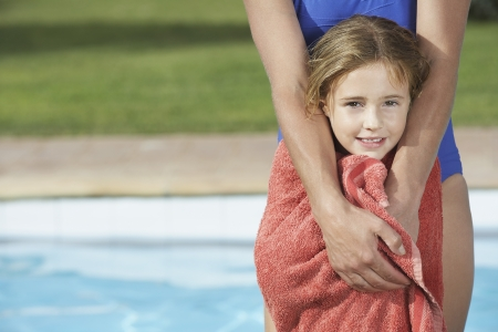 two piece swimsuits: Portrait of girl (5-6) wrapped in towel mother behind her