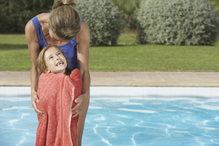 two piece swimsuits: Mother embracing daughter (5-6) wrapped in towel by pool