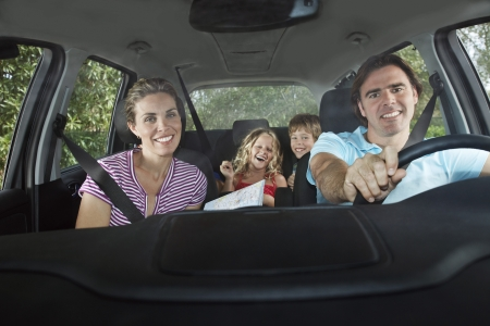 car driving: Family with two children (5-6) in car interior portrait LANG_EVOIMAGES