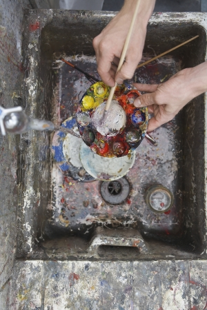 raised viewpoint: Artist rinsing palette at sink in studio view from above close-up of hands