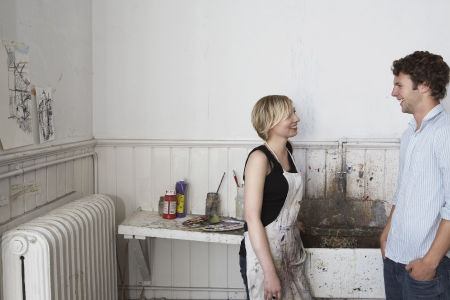 Two college students chatting by sink in art studio Stock Photo - 19078549
