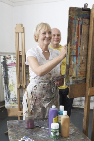 putney: Two mature students painting at easels in art class LANG_EVOIMAGES