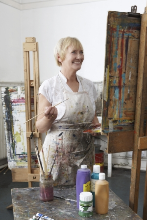 Mature female artist painting at easel in art studiocanvas in studio Stock Photo - 19078553