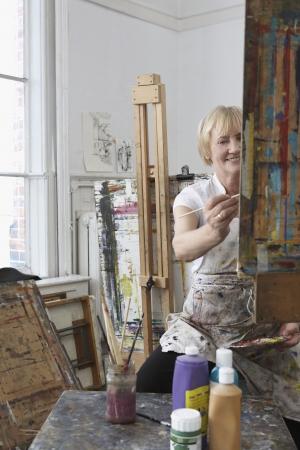 putney: Mature female artist painting at easel in art studio