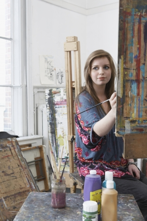 Young female art student painting at easel in art studio Stock Photo - 19078555