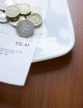 tipping: Pound coins and bill on plate close-up