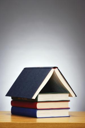 Books arranged in shape of house studio shot Stock Photo