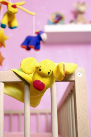 glove puppet: Crib with toys focus on foreground