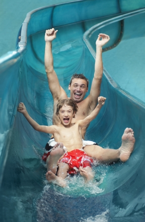WATER SLIDE: Father and son (7-9) with arms outstretched on water slide