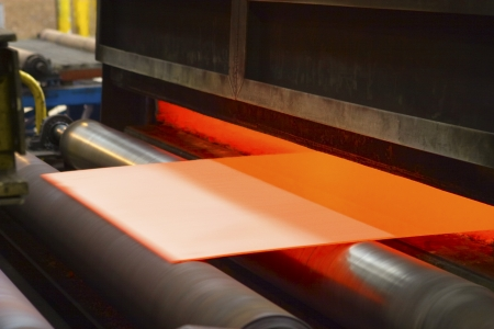 Sheet of orange-coloured material being fed through machine Stock Photo - 19078700