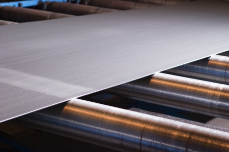Continuous sheet of metallic material being fed through machine Stock Photo - 19078701