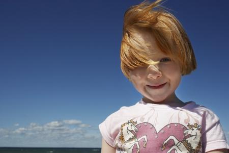 ginger haired: Portrait of ginger haired girl (5-6) against blue sky