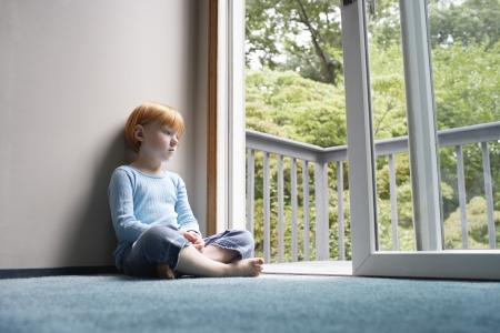 balcony door: Ni�a (5-6) que se sienta con las piernas cruzadas en la alfombra mirando a trav�s de la puerta del balc�n