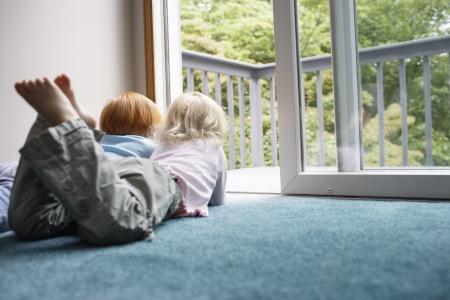 balcony door: Hermanas (3-6) que mienten en la alfombra mirando a trav�s de la puerta del balc�n LANG_EVOIMAGES