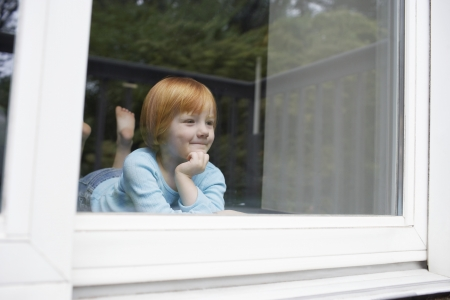 looking through window: Young girl (5-6) indoors looking through window LANG_EVOIMAGES