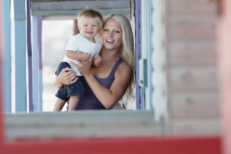 european ethnicity: Young mother holding son (1-2) on outdoor porch portrait