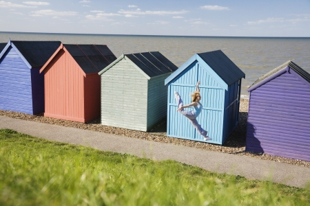 Woman jumping in front of beach hut Stock Photo - 19078940