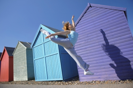 Woman jumping in front of beach huts Stock Photo - 19078941