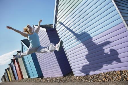 jambes �cart�es: Femme sautant en face de cabines de plage