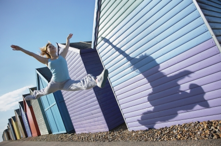 Woman jumping in front of beach huts Stock Photo - 19078942